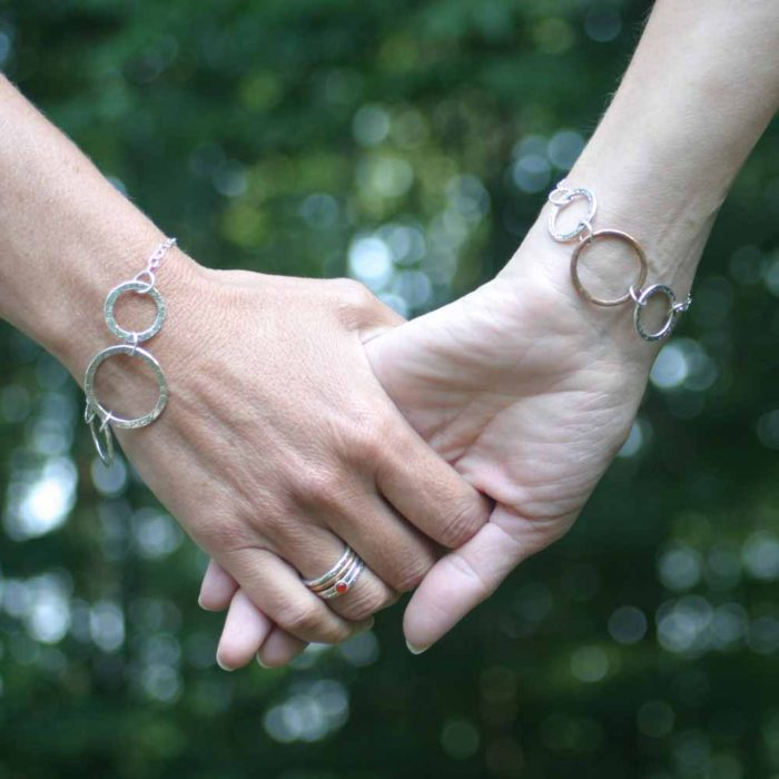 Friends holding hands with Connection bracelets